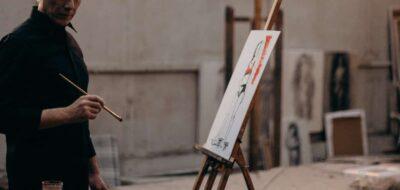 Uomo che dipinge davanti a cavalletto